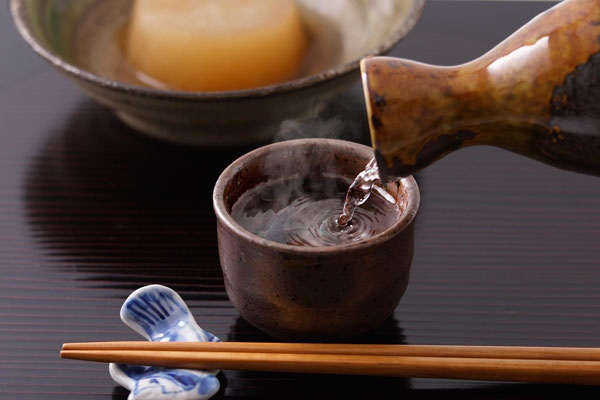 Chopsticks, Japanese sake, and Japanese foods on the tatami