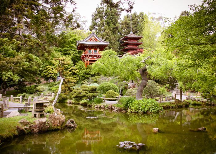 The five storied tower in front of the green and blooming flowers, Japanese style houses, and Taiko-bashi Bridge